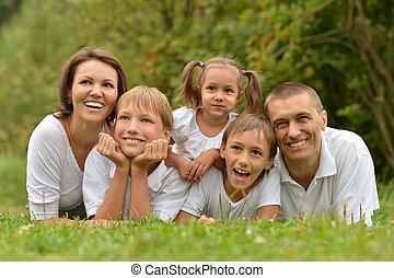 family lying on green grass