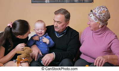 Big happy family with a baby her mother and grandparents...