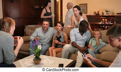 Three generations of happy international family blithely talking together in cozy home interior