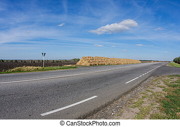 Big hay stack and a road daytime landscape