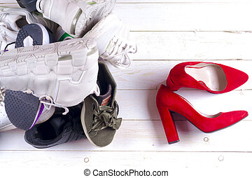 Big heap of different sports shoes and red high heel women's shoes on white background.