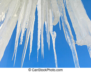 Big icicles on blue sky background