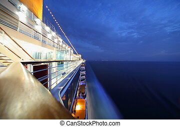 big illuminated cruise ship riding in evening. wide angle.