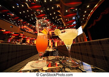big illuminated hall. coaches and tables. wineglass and glass with drinks in center of image. focus on top of glass. wide angle.