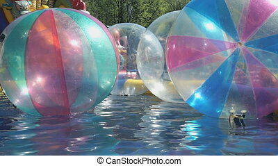 Big inflatable balls floating on the water in pool