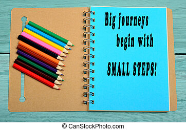 Big journeys begin with small steps written on notebook