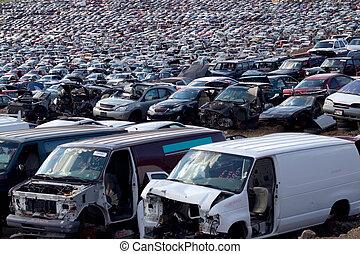 Huge junk yard filled with broken cars and vans