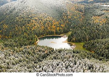 big lake in the middle of mountains during autumn