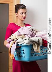 Big laundry basket - Overworked beautiful woman is carring ...