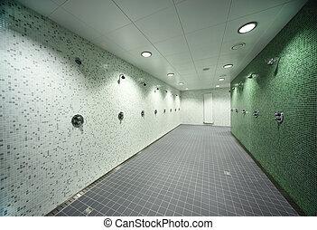 big, light, empty public shower room, green tile on walls,...
