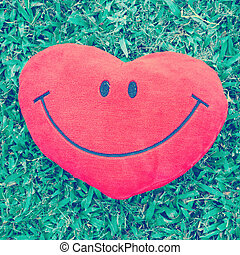 Big love heart shape pillow on green grass