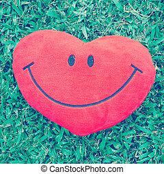Big love heart shape pillow on green grass