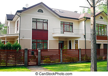 big luxury house with fence and green grass