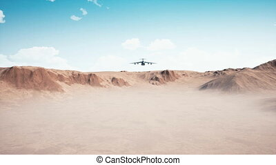 Big military freighter aircraft flying low over desert -...