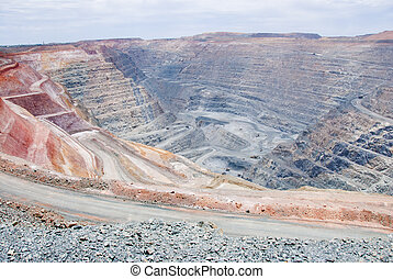 Big mine pit with little dump trucks and reddish soil - One...