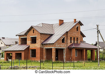 Big modern two-storied not finished new brick family cottage house with steep brown shingled roof, garages, high chimneys on blue sky background. Construction, investment and real property concept.