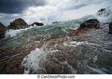 Big ocean wave breaking the rocks