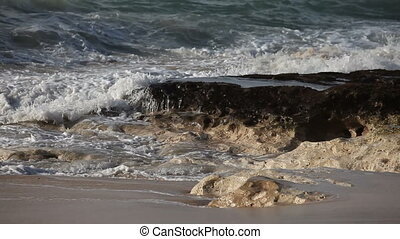 Big ocean wave crashes down on a stone