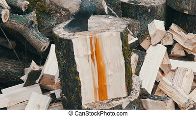 Big old wooden ax chops down tree trunks on the background...