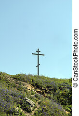 Big old wooden Orthodox cross on a hill on a clear blue cloudless sky on a summer day