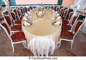 Big oval dinner table with candlestick, copper and empty dishes: plates with placemat, forks, knives and goblets
