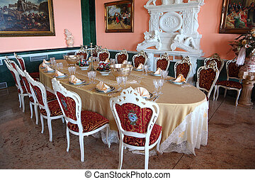 Big oval dinner table with empty dishes: plates with placemat, forks, knives and goblets