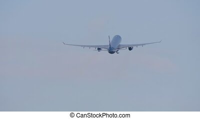 Big passenger airliner gains height after take off and flies away