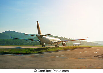 Big passenger airplanes on runway strip are taxiing for take-off