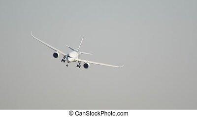 Big passenger plane flying in the gray sky