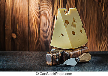 big piece of milk maasdam cheese with knife on little vintage wooden cutting board wooden background