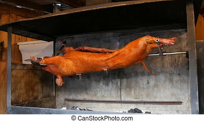 Big pig on a spit. Smoked and fried pig carcass at the medieval Christmas market in Munich. Whole roasted pork cooked with fire and charcoal, Food street festive of traditional European cuisine