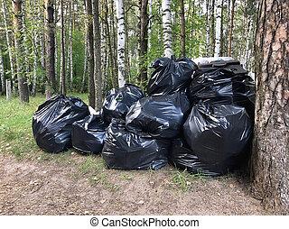 Big pile of garbage plastic bags outdoors in woods