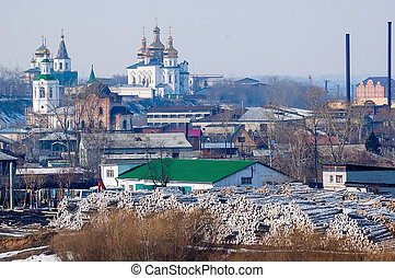 Big pile of logs and two churches. Tyumen. Russia