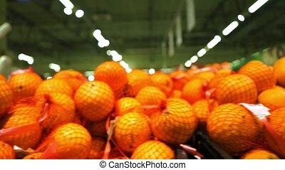 Big pile of oranges in a supermarket, dolly shot