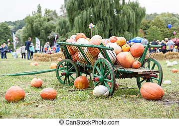 Big pile of pumpkins on hay in a wooden cart
