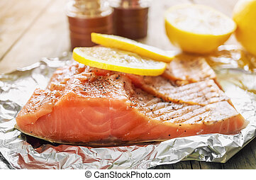 Big pink piece of salmon with herbs and lemon rests on a shiny piece of foil.