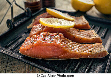 Big pink slice of salmon with herbs and lemon rests on a black grill pan.