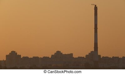 Big pipe on city skyline at sunset - industry view