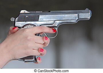 Female hands with manicure on nails, hold the big pistol.