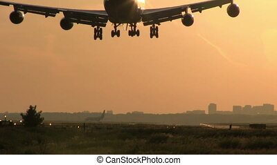 Big plane landing at sunset