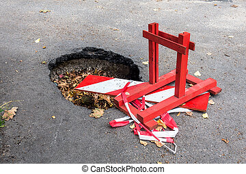 Big pothole on the road and warning sign. Road under constructon