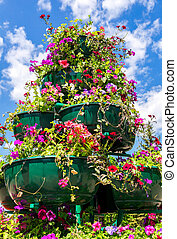 Big pots with decorative flowers against the blue sky in sunny day
