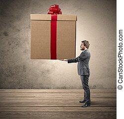 Big present - Elegant businessman holding a big Christmas ...