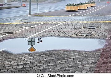Big puddle on the sidewalk in city