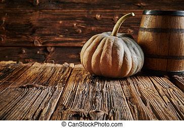 Big pumpkin and oak barrel in wooden room