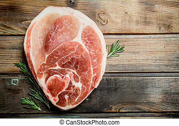 Big raw piece of pork meat with rosemary.