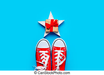 big red gumshoes and beautiful gift on star shaped toy on the wonderful blue background