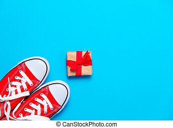 big red gumshoes and beautiful gift on the wonderful blue background