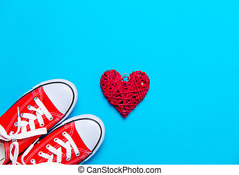 big red gumshoes and beautiful heart shaped toy on the wonderful blue background