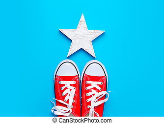 big red gumshoes and beautiful star shaped toy on the wonderful blue background